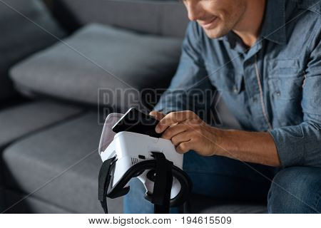 Using smartphone. Enthusiastic unconventional focused guy sitting on a couch and testing new gear he purchasing for virtual reality experience