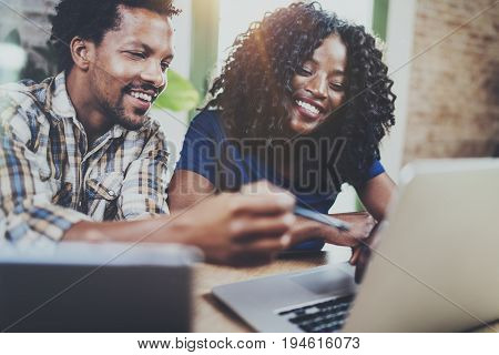 Happy smiling african american couple working together at home.Young black man and his girlfriend using laptop at home in the living room. Horizontal, blurred background.Flare