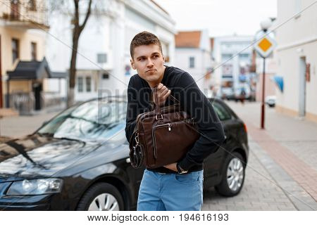 Young Man Stole A Leather Bag On The Background Of A Car