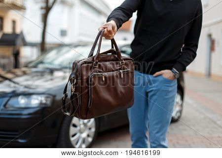 Male Businessman Giving Away Leather Bag On Background Of Car