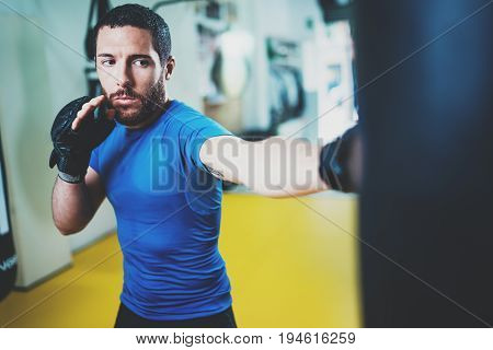 Young boxer man doing some training on punching bag at gym. Bearded caucasian boxer training with punching bag in gym.Concept of a healthy lifestyle.Horizontal