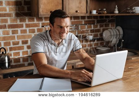 Office is everywhere. Optimistic devoted talented guy working as a freelancer and relying emails while sitting at the table in the kitchen