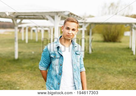 Happy Young Man In Jeans And A White T-shirt Near White Canopies In The Nature