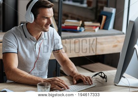 White collar. Wonderful handsome cheerful guy wearing headphones while typing something on his computer and working on another challenge in the office