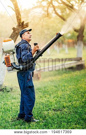 Industrial Farm Worker Gardening And Spraying Pesticide