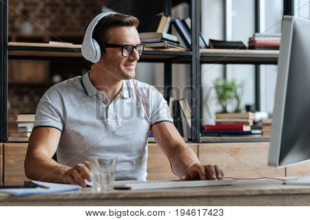 Savvy employee. Handsome cheerful persistent guy sitting at his workplace and using his computer while wearing headphones