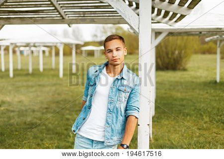 Handsome Young Man In A Denim Jacket And White Shirt Outdoors