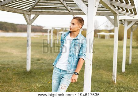 Handsome Young Man With Torn Jeans And A Denim Jacket Near A White Wooden Beach Canopy In The Open A
