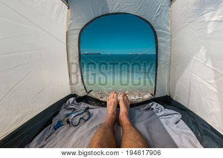 Traveler Man Lying In Tent With A View Of Sea Summer Beach Holiday Vacation Concept. View Of Legs. Point Of View Shot