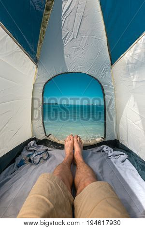 Tourist Man Lying In Tent With A View Of Sea Summer Beach Holiday Vacation Concept. View Of Legs. Point Of View Shot
