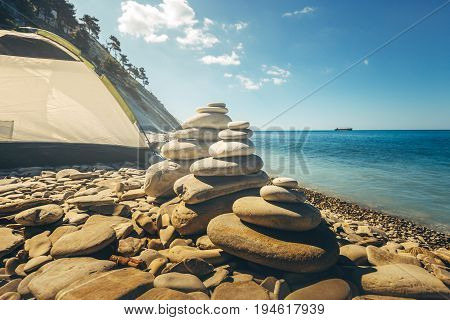 Stone Zen Pyramids At Beach With Tourist Tent On A Background. Concept Of Harmony And Balance