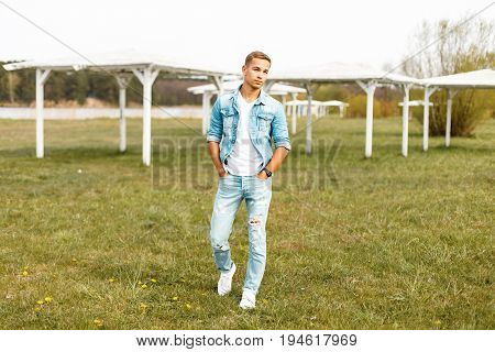 Handsome Young Man In A Denim Jacket And White T-shirt With Torn Jeans Walking In Nature