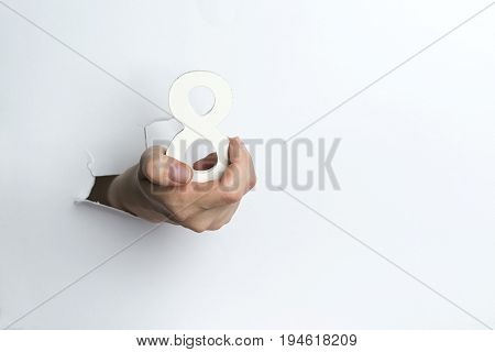 Female Hand Holding Up The Number Eight A White Background.