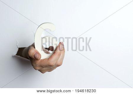 Female Hand Holding A Six Figure White Background.