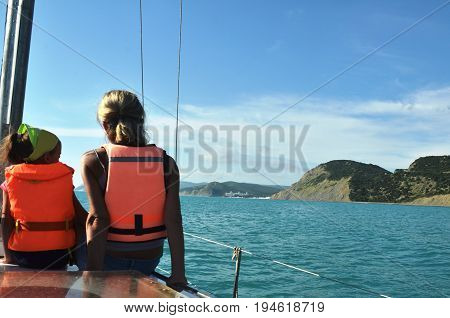 Boat trip on yacht. Young woman with girl in lifejackets sits on bow of yacht and admires sea view. Slight blur