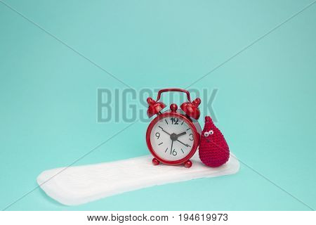 Red alarm clock smile crochet blood drop and daily menstrual pad. Menstruation sanitary woman hygiene. Woman critical days gynecological menstruation cycle. Medical conception photo