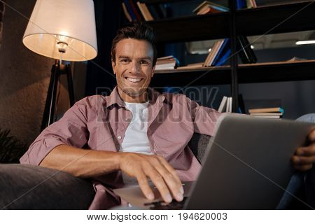 Chilling at my place. Easy going witty handsome man sitting on a couch and communicating with his friends while checking his social media
