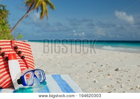 bag, diving mask and suncream on tropical beach