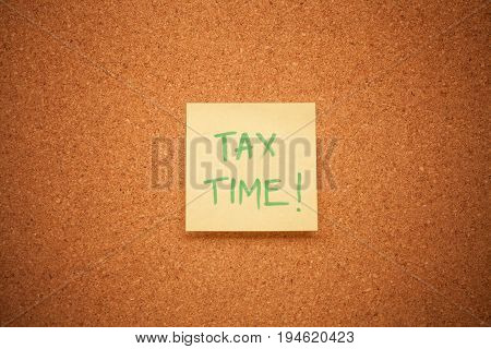 Sticky note on a cork board reading 'Tax Time'.