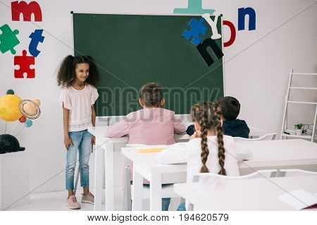 Smiling African American Schoolgirl Standing Near Chalkboard And Looking At Classmates Sitting At De