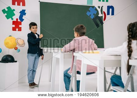 Schoolboy standing at chalkboard and looking at classmates sitting at desks
