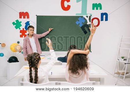 Schoolboy Holding Chalk And Pointing At Blackboard While Classmates Raising Hands