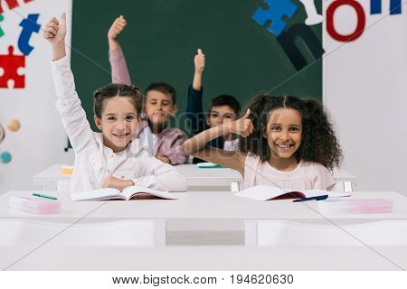 Cheerful Multiethnic Schoolkids Showing Thumbs Up While Sitting At Desks In Classroom