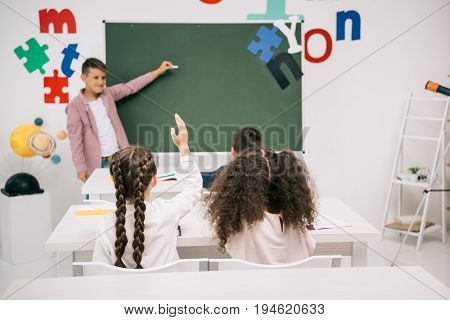 Back View Of Classmates Looking At Schoolboy Answering Near Blank Chalkboard
