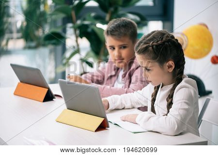 Cute Caucasian Schoolkids Using Digital Tablets While Studying Together In Class