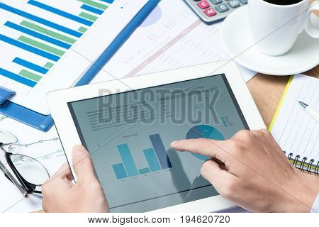 Close-up of businessman looking at business document in touchpad