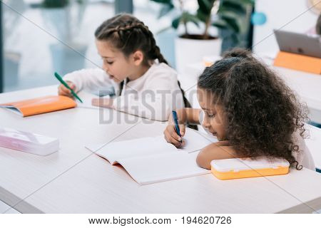 Adorable multiethnic schoolgirls writing and studying at desk in class
