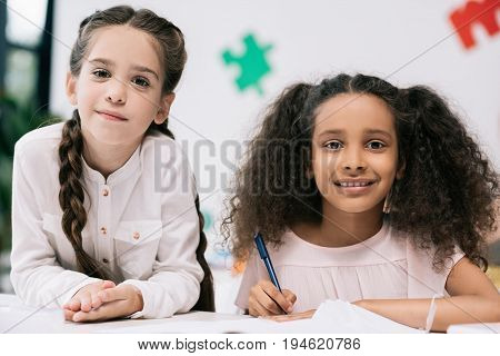 Adorable Multiethnic Schoolgirls Smiling At Camera While Studying Together In Classroom