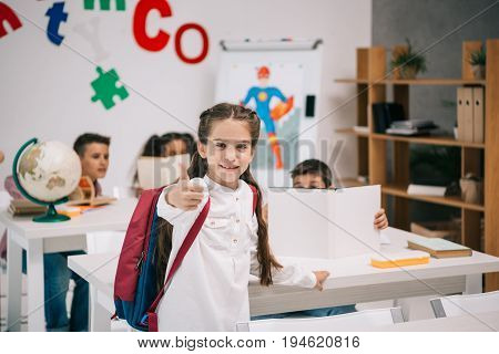 Cute Smiling Schoolgirl Showing Thumb Up While Classmates Studying Behind