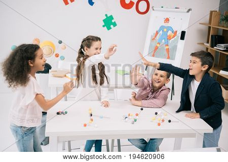 Multiethnic schoolkids giving high five while studying with molecular model in classroom