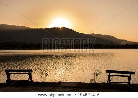 Sunshine on the surface And empty chairs/Silhouette of chairs and Mountain  with an orange tropical sunset