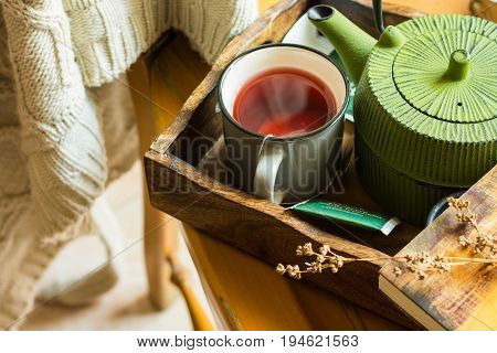 Mug with hot red fruit tea green pot book on tray knitted sweater hanging over wooden chair cozy atmosphere autumn fall