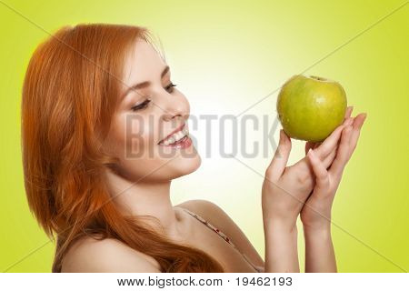 young beauty woman with apple on green background