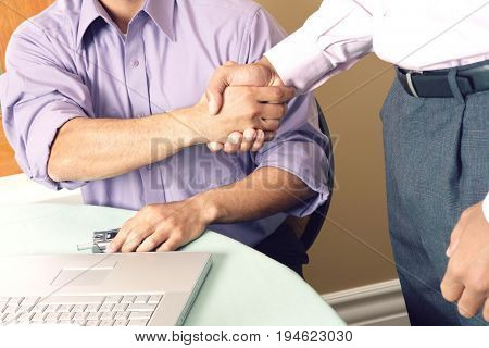 Two business men shaking hands in office, mid section