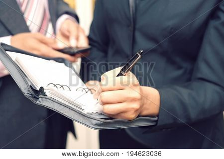 Business woman writing in diary, mid section