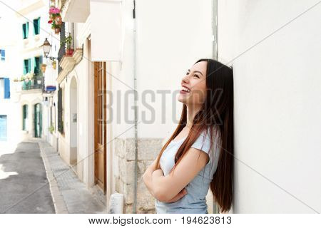 Side Of Beautiful Woman Standing In Street Laughing With Arms Crossed