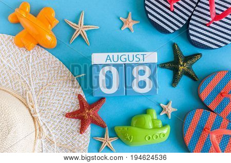 August 8th. Image of August 8 calendar with summer beach accessories and traveler outfit on background. Summer day, Vacation concept.