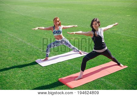 Beautiful sporty fit yogini women practices yoga asana - warrior pose. Group of happy young people tretching in yoga on the stadium.