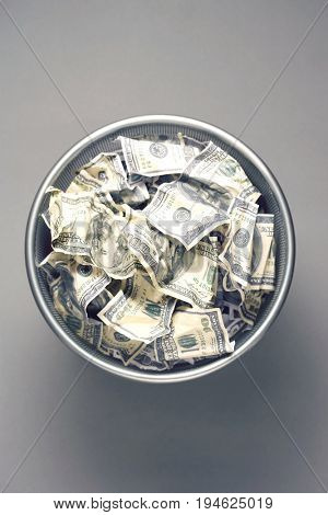 Dollar bills in wastebasket, view from above