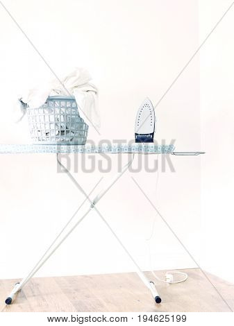 Iron and laundry basket on ironing board against white wall