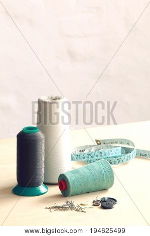 Spools of thead, pins and measuring tape on table