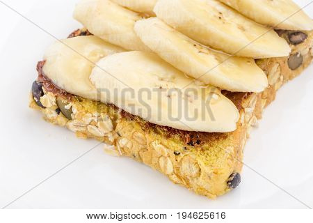 Chocolate and sliced banana on open wholewheat sandwich bread topped with honey in morning breakfast healthy eating concept.