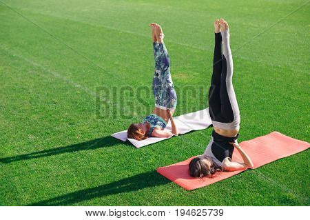 Yoga women practising her strength and balance. Young women doing yoga in morning time with the sun lighting on the stadium.