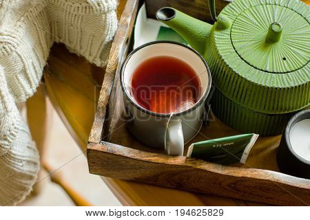 Mug with warm red fruit tea paper bags green pot in trey white knitted sweater hanging over old wooden chair fall autumn tranquility