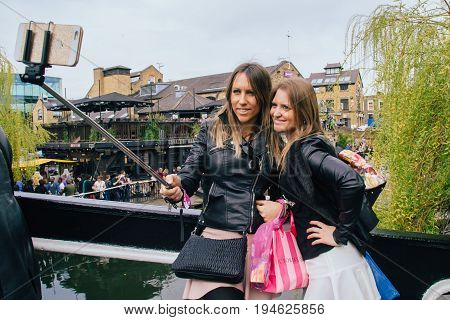 UK London - 08 April 2015: The Camden Market in London England. Unknown girls make selfie on the background Camden Market