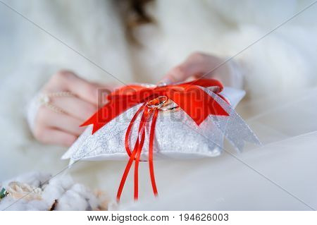 Golden wedding rings on red, crimson and white ring pillow with red crimson bow and ribbons in hands of bride